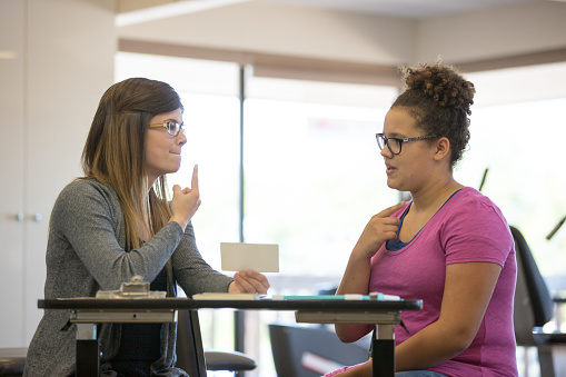 A young adult female speech therapist is helping a teenage patient inside of a clinic