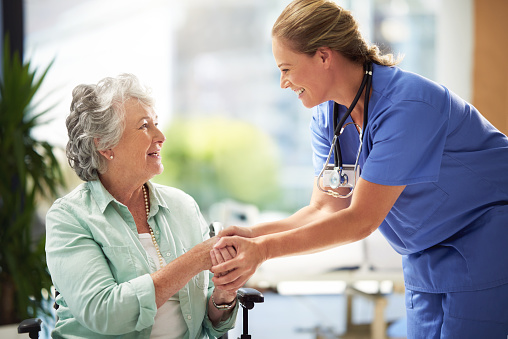Shot of a doctor shaking hands with a smiling senior woman sitting in a wheelchair